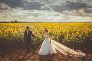 Couple mariés devant champ tournesol